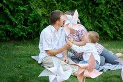 年轻家庭坐草在有玩具的一个公园 免版税库存照片