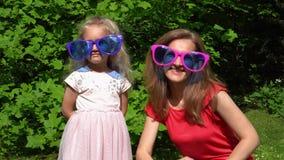 家庭女孩母亲和女儿在巨大的太阳镜和展示手指举起 影视素材