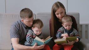 家庭妈妈、爸爸和两双胞胎读了书坐沙发 家庭读书时间 股票视频