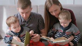 家庭妈妈、爸爸和两双胞胎读了书坐沙发 家庭读书时间 股票录像
