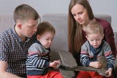 家庭妈妈、爸爸和两双胞胎读了书坐沙发 家庭读书时间 免版税库存图片