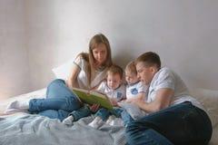 家庭妈妈、爸爸和两双胞胎读了放置在床的书 家庭读书时间 免版税库存图片