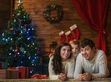 家庭妈妈、爸爸和儿子在一个装饰的房子里庆祝圣诞节 库存照片