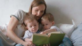 家庭妈妈和两个双胞胎小孩读了放置在床的书 家庭读书时间 影视素材