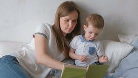 家庭妈妈和她的儿子小孩读了放置在床的书 家庭读书时间 股票录像