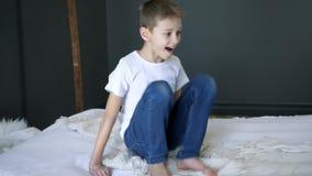 家庭娱乐活动,男孩在慢动作的床上跳跃并且获得乐趣在室 影视素材