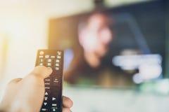 家庭娱乐活动 手举行聪明的电视遥控有电视迷离背景 库存图片