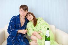 家庭对沙发汽酒年轻人 免版税库存图片