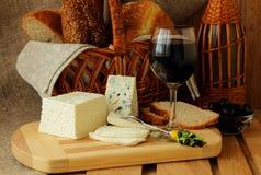 家庭希腊白软干酪、青纹干酪、酒和面包 库存图片