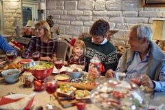 家庭庆祝圣诞节并且在假日享用 免版税库存图片