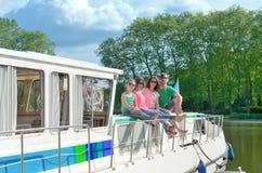家庭度假、暑假旅行在驳船小船在运河,愉快的孩子和父母获得乐趣在河巡航旅行在居住船 库存照片