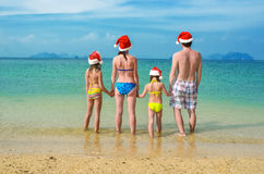 家庭度假在圣诞节和新年假日,愉快的父母和孩子圣诞老人帽子的获得乐趣在海滩 库存图片
