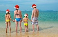 家庭度假在圣诞节和新年假日,愉快的父母和孩子圣诞老人帽子的获得乐趣在海滩 免版税库存照片