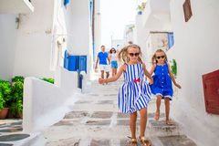 家庭度假在欧洲 父母和孩子在典型的希腊传统村庄街道在米科诺斯岛海岛上,在希腊 库存照片