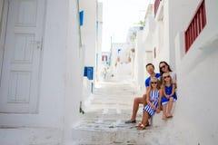 家庭度假在欧洲 父母和孩子在典型的希腊传统村庄街道在米科诺斯岛海岛上,在希腊 图库摄影