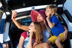家庭度假手提箱女孩男孩孩子行李蓝色桃红色橙色房子太阳夏天行李汽车准备好假日绿化trank起动妇女 库存照片