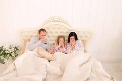 年轻家庭得到了病态或不适在家打喷嚏在床上 图库摄影