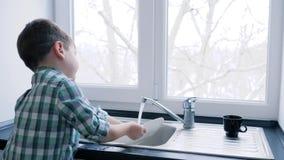 家庭惯例,小男孩洗涤在水槽的碗筷在窗口背景  股票视频