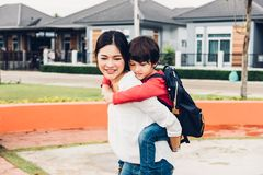 家庭愉快的儿童孩子儿子男孩幼儿园乘驾piggyba 库存图片