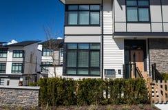 家庭房子在郊区与具体人行道和在前面的柏油路街道  住宅房子 库存照片