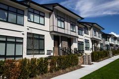 家庭房子在郊区与具体人行道和在前面的柏油路街道  住宅房子 免版税库存照片