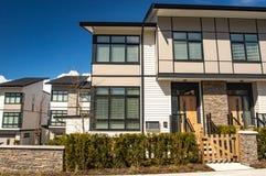 家庭房子在郊区与具体人行道和在前面的柏油路街道  有停车场的住宅房子 库存图片