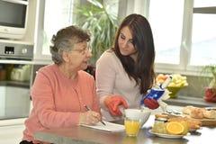 家庭护工helÄ 砰做纵横填字谜的一名资深妇女 免版税库存图片