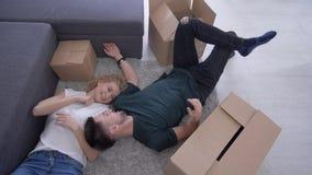 家庭拆迁,有女孩的愉快的可爱的人在箱子和梦想中的地板上在关于未来住所改善 股票视频