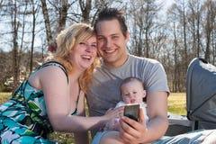 年轻家庭拍与智能手机的一张照片 库存照片