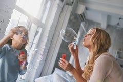 家庭接合 母亲和女儿吹的肥皂泡,当s时 免版税图库摄影