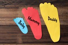 家庭措施他们的与五颜六色的纸的脚在木背景 免版税库存图片