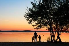 家庭握手在树下在日落 免版税库存照片