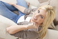家庭放松的微笑的沙发妇女年轻人 免版税库存图片