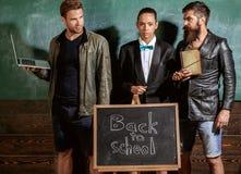 家庭教师在有题字的黑板附近合作身分回到学校 老师准备工作,拿着学校设备 库存照片