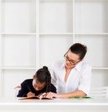 家庭教师帮助的女小学生 免版税库存图片