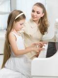 家庭教师教小孩弹钢琴 免版税库存照片