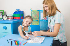 家庭教师检查在一个五年女孩的片断做的工作 免版税库存照片