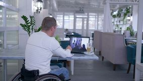 家庭教育,轮椅的资深被致残的人在笔记本写笔记,当观看网上训练在膝上型计算机时 股票录像