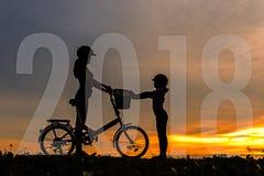 家庭新年好卡片2018年 现出轮廓骑自行车的人可爱的家庭在海洋的日落 图库摄影