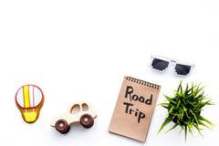 家庭旅行概念 太阳镜,绿色植物,空气轻快优雅曲奇饼,汽车玩具 旅行在笔记本的手字法在白色 图库摄影