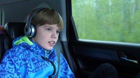 家庭旅行 家庭在高速公路驾驶 在汽车的青少年的开会和听到音乐通过耳机 影视素材