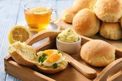 家庭早餐-家制面包卷,茶,煮沸了鸡蛋和大蒜草本黄油 库存图片
