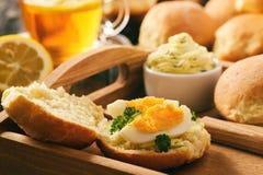 家庭早餐-家制面包卷,茶,煮沸了鸡蛋和大蒜草本黄油 免版税库存图片