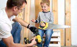家庭时间:爸爸显示他的儿子手工具、一把黄色螺丝刀和一把引形钢锯 他们需要操练和操练委员会为 库存图片