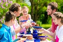 家庭有咖啡和蛋糕在庭院在房子 免版税库存图片