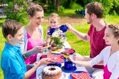 家庭有咖啡和蛋糕在庭院在房子 库存照片