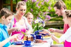家庭有咖啡时间在吃蛋糕的庭院 库存图片