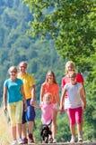 家庭有在道路的步行在森林 免版税图库摄影
