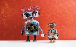 家庭机器人 大机器人妈妈握一个小儿童机器人的手 创造性的设计未来派靠机械装置维持生命的人在红色墙壁上戏弄 免版税库存照片