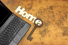 家庭标志、钥匙和膝上型计算机在老地图背景 库存照片